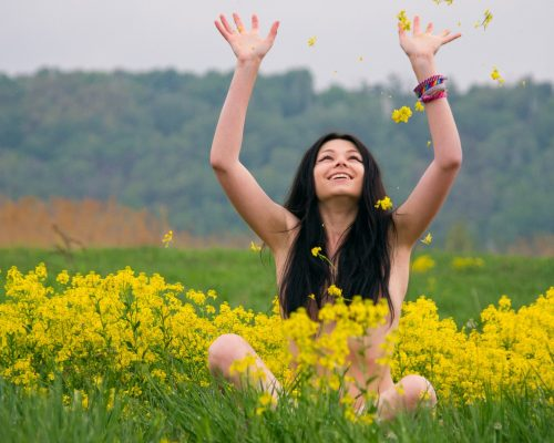 ?heerful beautiful naked woman smiles in the floral meadow. Girl sits in yellow flowers.